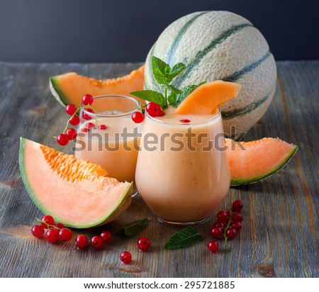 Healthy smoothie vitamins drink with red currant fresh berries, mint and cantaloupe melon, shake with yogurt for breakfast on wooden rustic background, summer harvest beverage, diet concept - stock photo