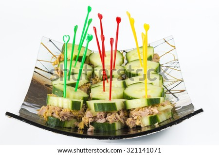 Healthy snack for diabetics: tuna and cucumber sandwiches or finger foods made of tuna sandwiched  in cucumber slices, arranged in a decorative curved glass plate. - stock photo