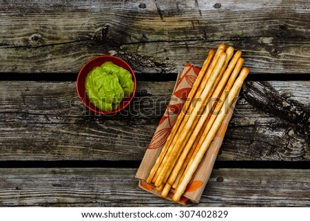 Healthy snack. Fresh guacamole dip with bread sticks over rustic wooden background with space for text. Top view.  - stock photo