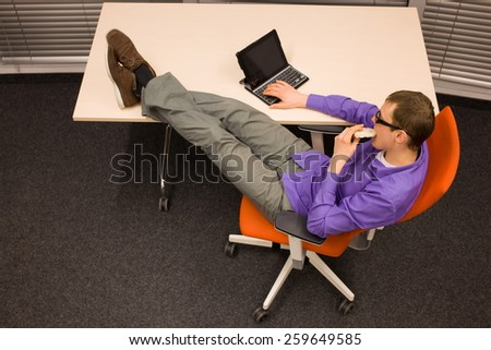 Healthy snack in workplace. Man sitting at with legs on the desk with tablet, eating corn waffle  in office  - stock photo