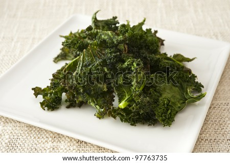 Healthy snack of a plate of roasted kale chips - stock photo