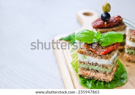 Healthy snack pieces of bread with cottage and vegetables on cutting board - stock photo