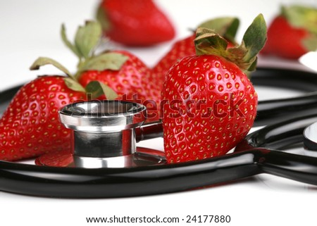 Healthy snack, strawberries. Stethoscope with strawberries isolated
