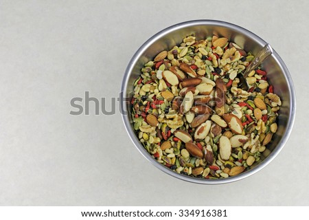 Healthy snack variety of dried fruit, seeds and nuts in a stainless steel bowl. Sunflower seeds, pumpkin seeds, pine nuts, almonds, goji, pistachios, and similar mixed