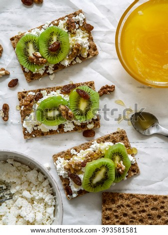Healthy snack with cheese cottage, kiwi and honey - stock photo