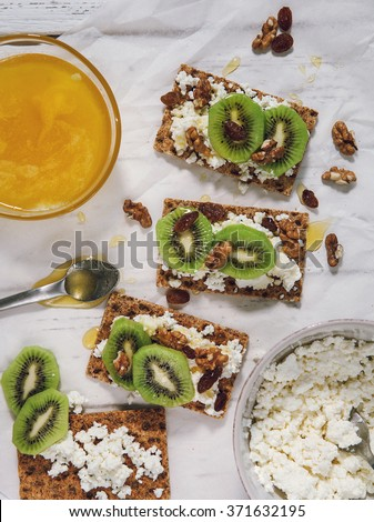Healthy snack with cottage cheese, kiwi and honey - stock photo