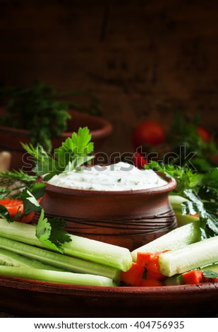 Healthy snacks: cucumber sticks, celery and carrots with ranch dressing, vintage wooden background, selective focus - stock photo