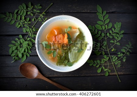 Healthy soup. Moringa leaves, tomato, carrot and lettuce on black wooden table. - stock photo
