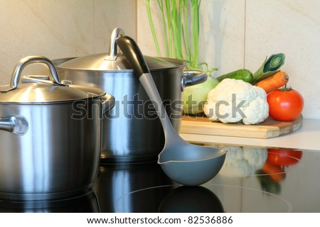 healthy soup with vegetables in the kitchen , pot on induction hob - stock photo