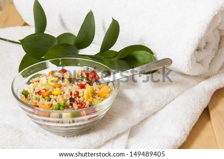 Healthy spa lunch of quinoa salad in a dish on a white towel - stock photo