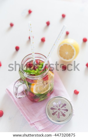 Healthy Spa Water with Fruit. Vitamin water with lemon, mint and raspberries in a jar with straw against a white wood background. - stock photo