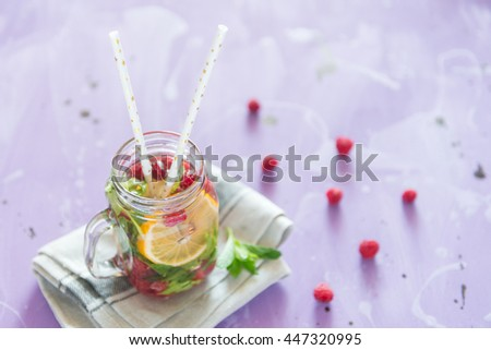 Healthy Spa Water with Fruit. Vitamin water with lemon, mint and raspberries in a jar with straw against a lilac wood background. Available space at right side. - stock photo
