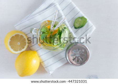 Healthy Spa Water with Fruit. Vitamin water with lemon, mint, celery and cucumber in a jar with straw against a white wood background. Available space at right side - stock photo