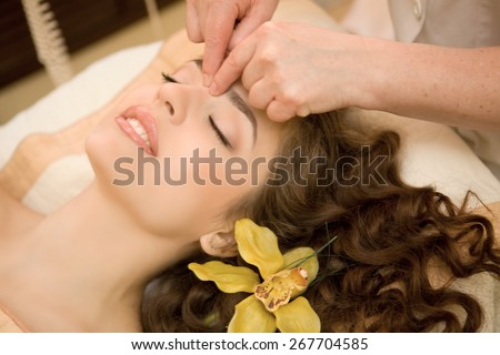 Healthy spa: young beautiful relaxing woman having a facial massage, with orchid in long brown hai - stock photo