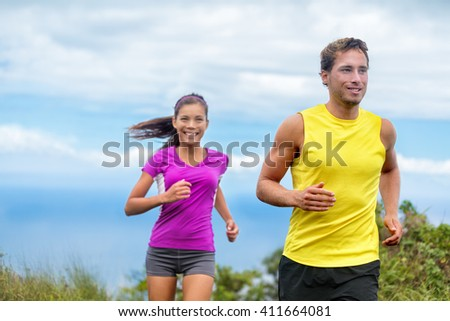 Healthy sports people trail running living an active life. Happy lifestyle couple of athletes training cardio together in summer outdoors. Multi-ethnic group Asian woman with handsome fit man trainer.