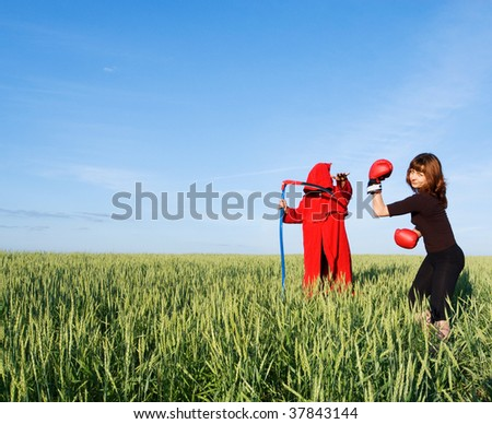 Healthy sporty girl and spooky figure in red hood with a scythe - stock photo