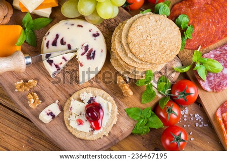 Healthy starters on rustic wooden cheese board - stock photo