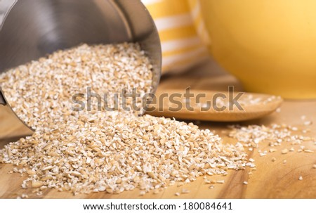 Healthy steelcut whole oats spilling out of a measuring cup - stock photo