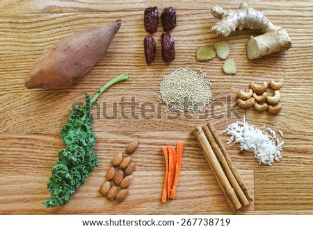 Healthy still life on wooden table with kale, quinoa, dates, ginger, coconut, cashews, almonds and cinnamon sticks