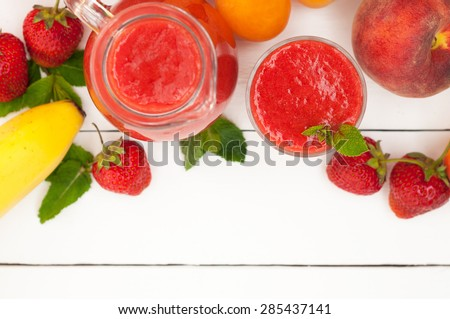 Healthy strawberry banana smoothie with mint in a glass and pitcher on white wooden background. Fresh fruits bananas, peaches and apricots background. Selective focus. Top view - stock photo