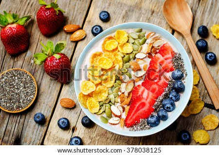 healthy strawberry smoothie bowl with fruits, cereals, seeds and nuts. toning. selective focus - stock photo