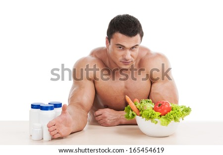 Healthy strong handsome man choosing healthy food instead of steroid. Sitting isolated on white background