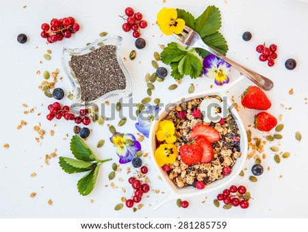 Healthy summer breakfast with chia seeds, granola, flowers and berry on white wooden background. Health and diet concept - stock photo