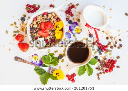Healthy summer breakfast with coffee, granola, milk, flowers and berry on white wooden background. Health and diet concept - stock photo