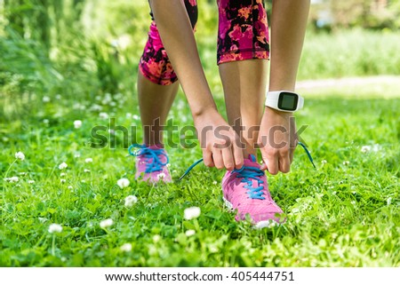 Healthy summer lifestyle - Girl runner getting ready for weight loss exercise tying running shoes laces wearing smartwatch activity tracker for an active living. Cute pink floral tights and outfit. - stock photo