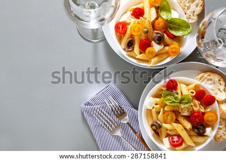 Healthy summer light pasta salad with fresh raw tomatoes, anchovies and capers. glasses with water - stock photo