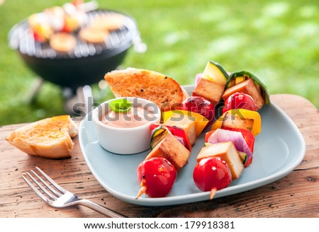 Healthy summer meal of halloumi and vegetable kebabs roasted over an outdoor barbeque in the garden and served with a savory sauce and toasted baguette on a picnic table