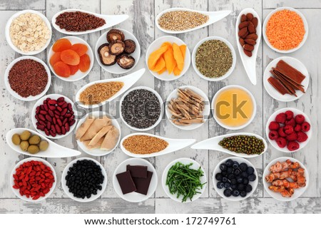 Healthy super food selection in porcelain bowls over distressed wooden background.  - stock photo