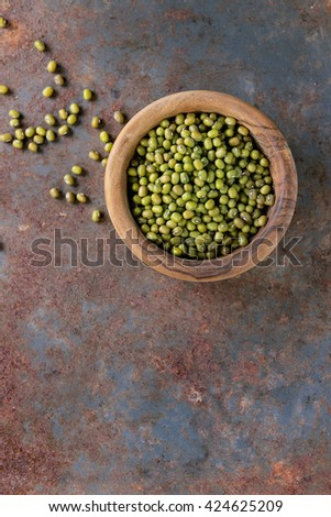 Healthy super food. Uncooked green mungo beans in olive wood bowl over old rusty iron background. Top view. With copy space - stock photo