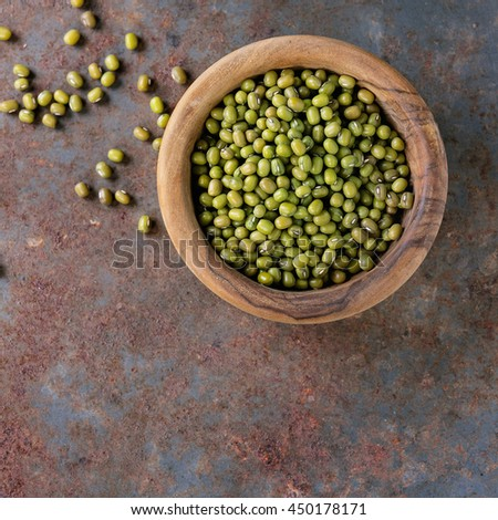 Healthy superfood. Uncooked green mungo beans in olive wood bowl over old rusty iron background. Top view. With copy spaceÃ?? Square image - stock photo