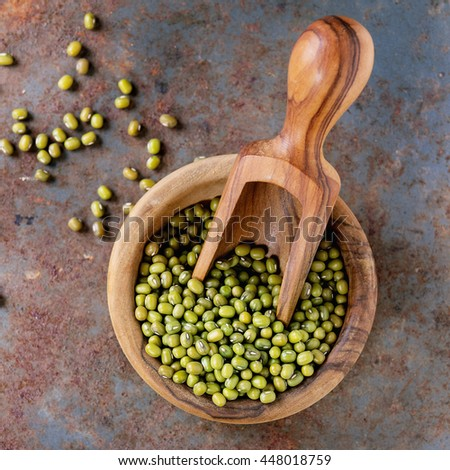 Healthy superfood. Uncooked green mungo beans in olive wood bowl with scoop over old rusty iron background. Top view. Square image - stock photo