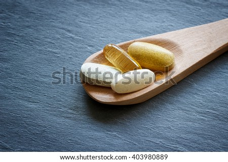 Healthy Supplements on wooden spoon with dark stone background