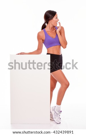 Healthy surprised brunette woman holding blank placard and looking away with her hand to her mouth while wearing violet and black gymnastic clothing, isolated - stock photo