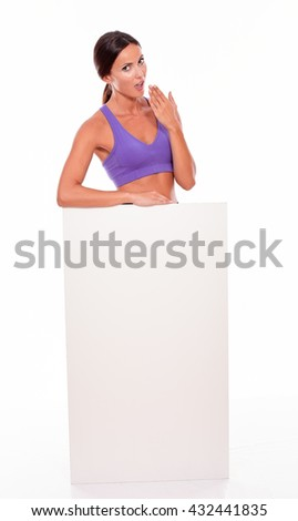 Healthy surprised brunette woman standing behind a blank placard and looking at camera, hand to her mouth while wearing violet gymnastic clothing on white background - stock photo