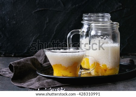 Healthy tapioca pearls pudding dessert with coconut milk and mango. Served in glass jars on vintage iron tray over old wooden table with black textile napkin. Dark rustic style. - stock photo