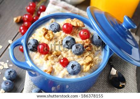 Healthy Tasty Homemade Oatmeal with Berries and glass of juice for Breakfast - stock photo