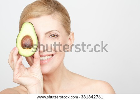 Healthy tips. Portrait of a happy healthy mid aged blonde woman laughing cheerfully covering her eye with a half of an avocado