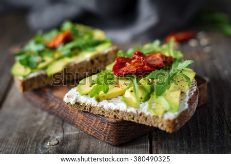 Healthy toast with goats cheese, avocado, arugula and sun dried tomatoes on rustic wooden table. Selective focus, close up - stock photo