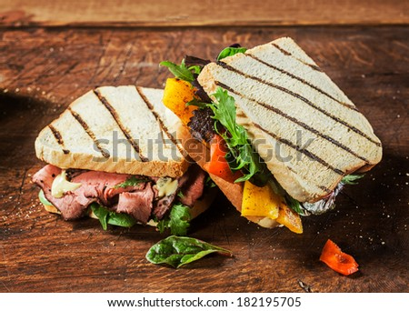 Healthy toasted and grilled sandwiches from a BBQ picnic with rare roast beef, cheese, pepper, rocket and spinach on a rustic wooden table,close up view - stock photo