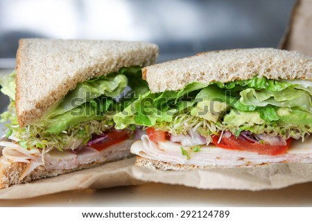 Healthy turkey, avocado, and sprouts sandwich on whole wheat lunch