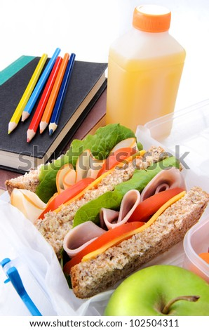 Healthy turkey ham sandwich with apple and school books - stock photo