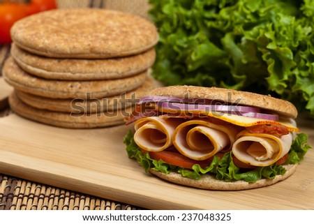 Healthy Turkey Sandwich on Whole Wheat Thin Sandwich Roll. Selective focus. - stock photo