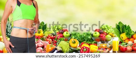 Healthy vegan diet. Woman measuring her body. - stock photo