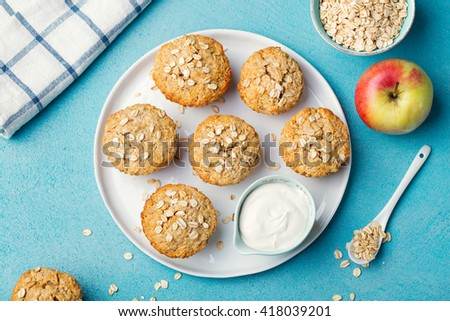 Healthy vegan oat muffins, apple and banana cakes with sour cream on a white plate Blue stone background Top view - stock photo