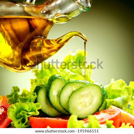 Healthy Vegetable Salad with Olive oil dressing. Pouring Olive oil. Healthy vegetarian food. Vegan. Diet, dieting concept. Lettuce, tomatoes, cucumbers. Organic bio food - stock photo