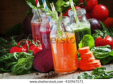 Healthy vegetable smoothie glass bottles with straws, vintage wooden background, selective focus - stock photo